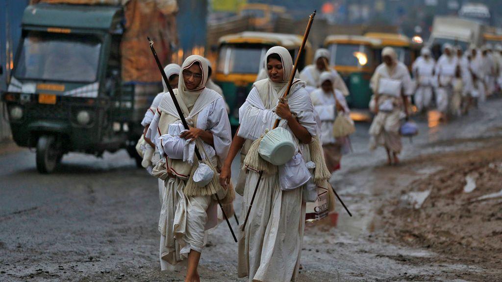 Las mujeres pertenecientes a la comunidad Jain caminan por una calle para recoger comida de los residentes locales que viven en las áreas cercanas, durante la madrugada en Ahmedabad, India