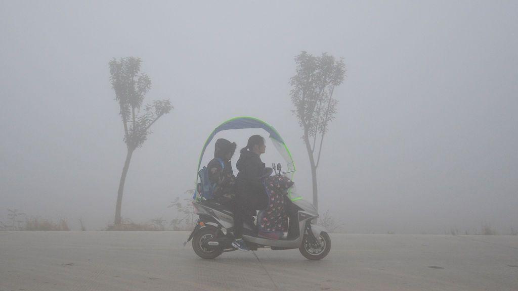 La gente monta un scooter más allá de los árboles en un día de niebla en una aldea en Fuyang, provincia de Anhui, China,