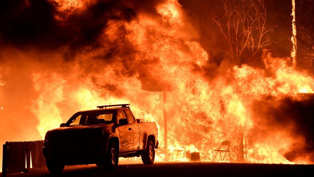 Las llamas se extendieron detrás de un vehículo desde un incendio de Santa Ana, arrastrado por el viento, llamado Thomas Fire en Santa Paula, California.