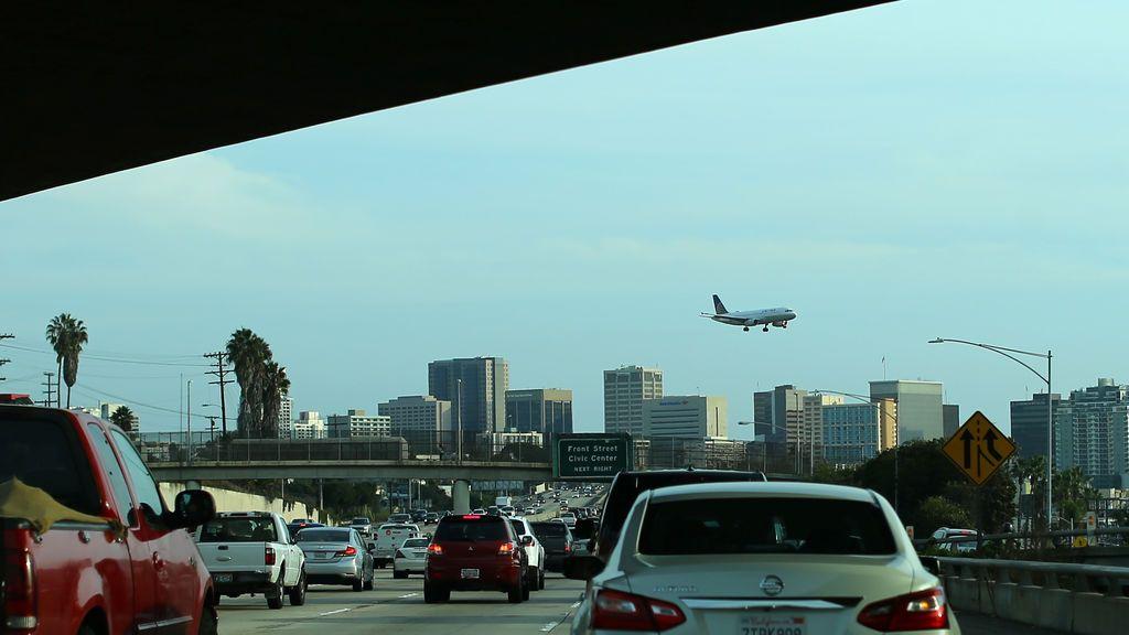 Los viajeros manejan a lo largo de una autopista cuando un avión se aproxima a aterrizar en San Diego, California, EE. UU