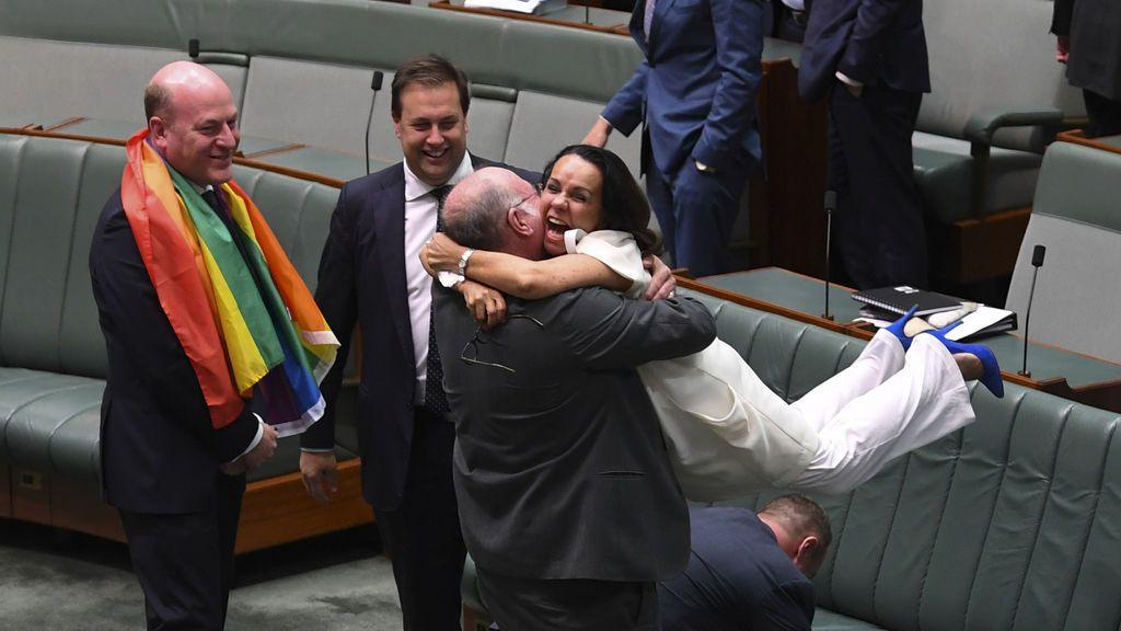El parlamentario liberal Warren Entsch levanta a la diputada laborista Linda Burney mientras celebran la aprobación del proyecto de ley de enmienda matrimonial en la Cámara de Representantes en la Casa del Parlamento en Canberra