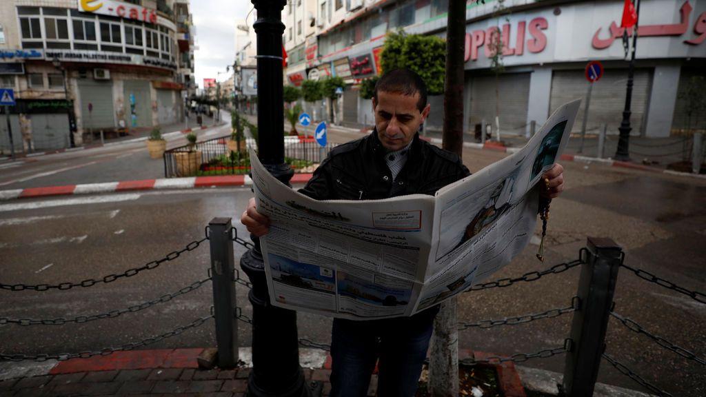 Un palestino lee un periódico durante una huelga general por la decisión del presidente estadounidense Donald Trump de reconocer a Jerusalén como la capital de Israel, en la ciudad cisjordana de Ramallah