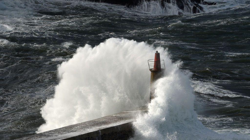 Las olas se estrellan contra un faro en el paseo marítimo de Viavelez en el norte de Asturias, España