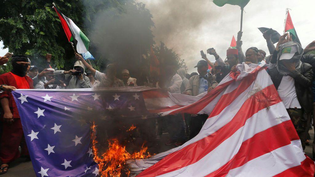 Miembros del Frente de Defensores Islámicos (FPI) queman una maqueta de la bandera estadounidense durante una protesta para condenar la decisión de Washington de reconocer a Jerusalén como la capital de Israel, frente a la embajada de EE. UU