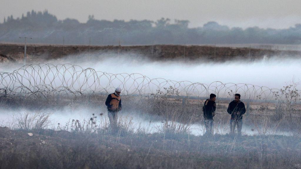 Manifestantes palestinos camina en medio de granadas de gas israelí durante enfrentamientos cerca a la frontera con Israel