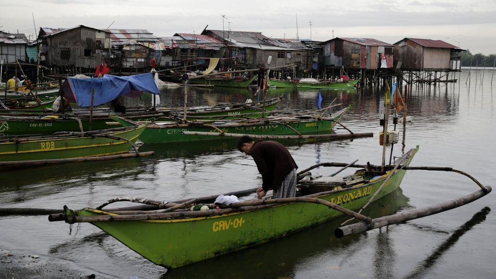 Un pescador asegura su bote hoy, martes 12 de diciembre de 2017, en la ciudad de Bacoor (Filipinas).