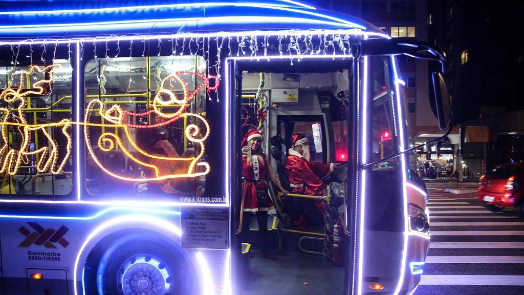 Un conductor vestido de Papá Noel conduce un autobús de la alcaldía de Sao Paulo decorado con luces de Navidad