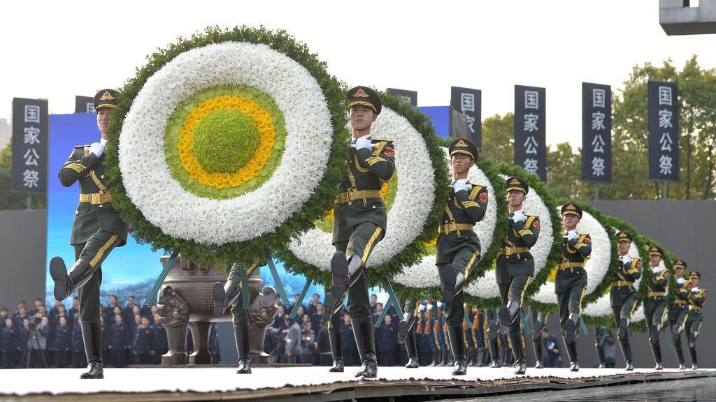 Policías paramilitares llevan coronas mientras marchan durante una ceremonia conmemorativa para conmemorar el 80 aniversario de la masacre de Nanjing de 1937, en el día conmemorativo nacional en Nanjing, provincia de Jiangsu