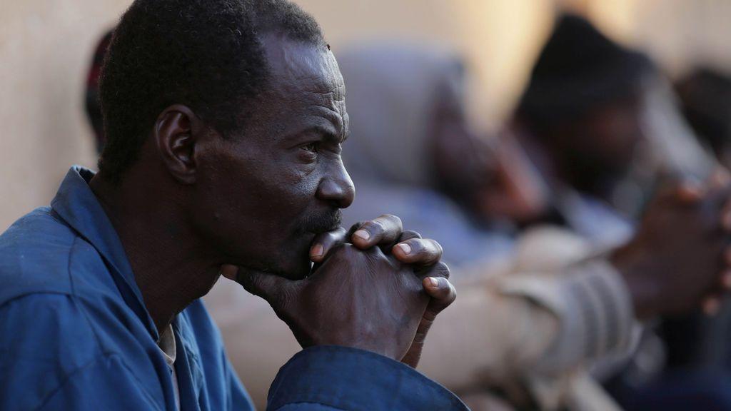 Un migrante espera sentado en un centro de detención de Libia
