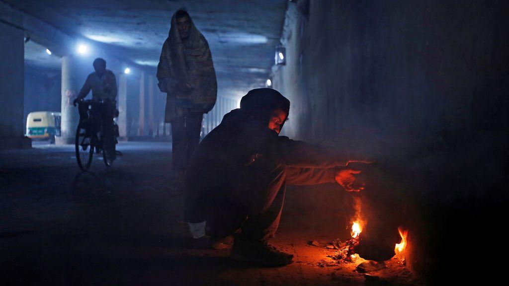 Un hombre calienta sus manos en el fuego realizado en una calle de la India