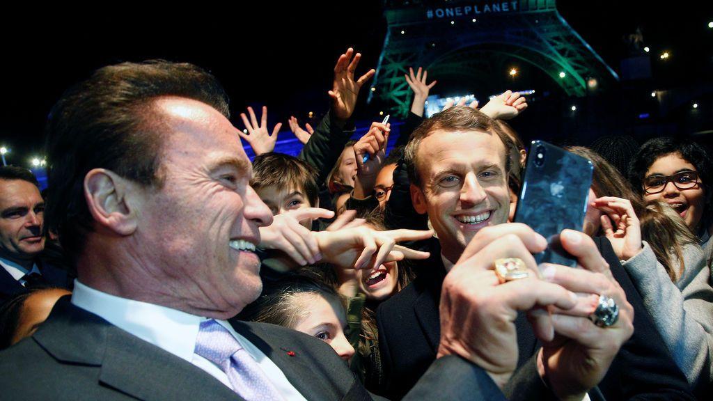 El presidente francés Emmanuel Macron (R) y el fundador del R20 y ex gobernador del estado de California Arnold Schwarzenegger se toman una selfie con jóvenes frente a la Torre Eiffel iluminados en verde, a bordo de un crucero en el río Sena desde One Planet Summit, en París , Francia