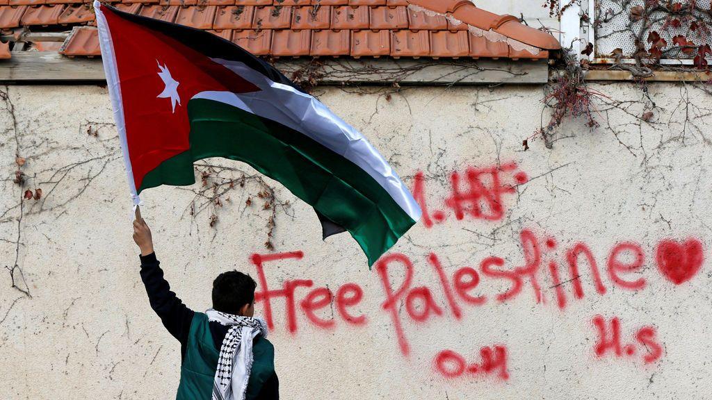 Un niño sostiene la bandera nacional jordana durante una protesta cerca de la Embajada de EE.UU.