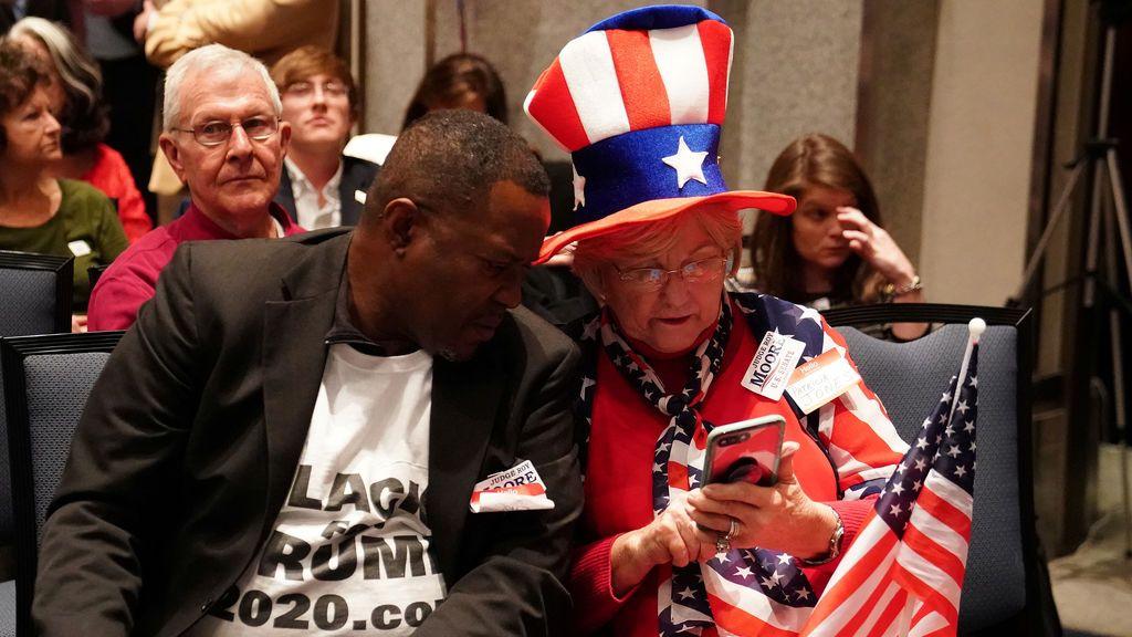 Las personas miran los resultados en un teléfono en la fiesta nocturna de la elección del candidato republicano al Senado estadounidense Roy Moore en Montgomery, Alabama, EE. UU