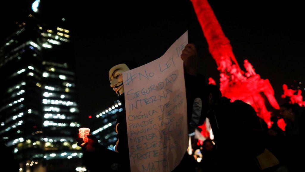 Un activista con una máscara sostiene una vela durante una protesta contra un nuevo proyecto de ley de seguridad, la Ley de Seguridad Interna, en la Ciudad de México, México
