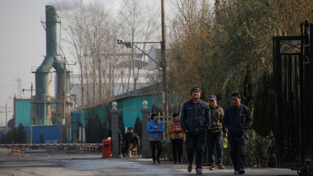 Humo sale de una chimenea cuando los trabajadores abandonan una fábrica en el condado rural de Gaoyi, conocido por su producción de cerámica, cerca de Shijiazhuang, provincia de Hebei, China