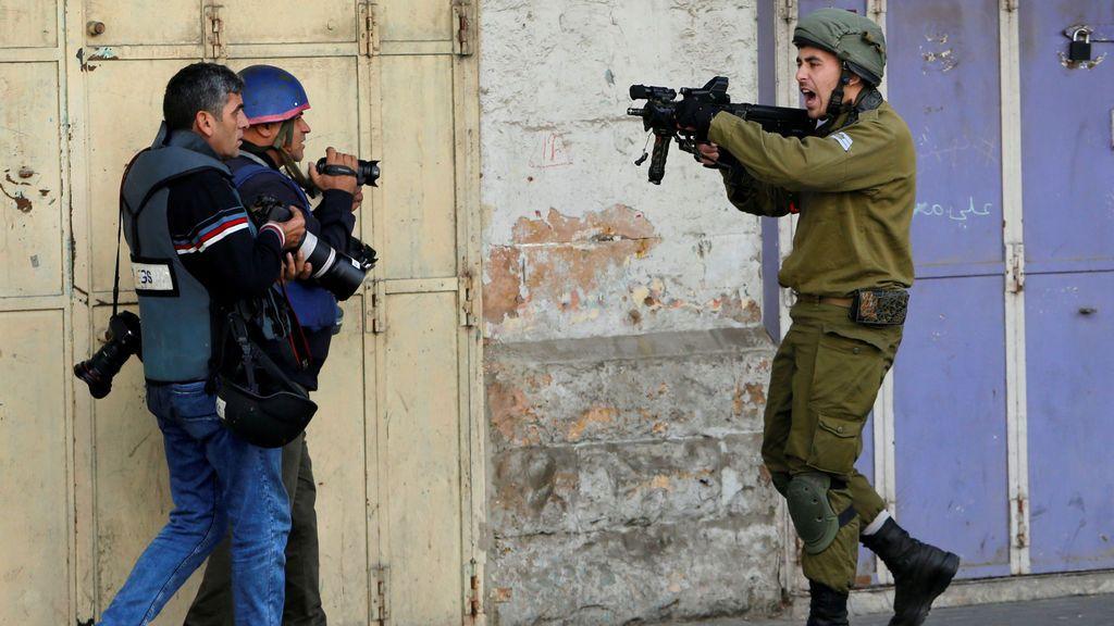 Un soldado israelí encañona a dos hombres durante las protestas por la decisión de Trump