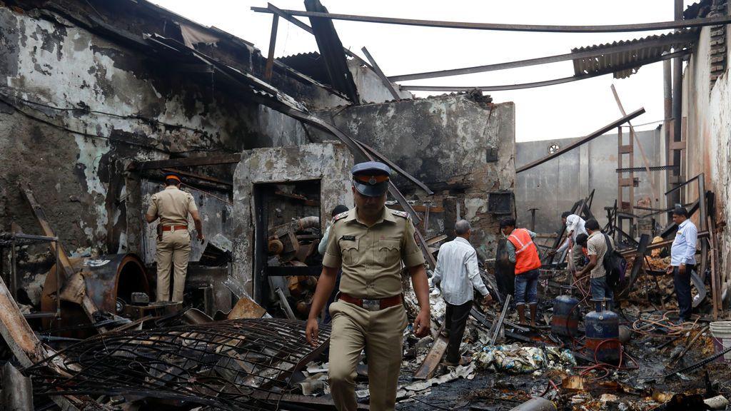 Policías y socorristas inspeccionan los escombros en un sitio dañado después de que estalló un incendio en una fábrica de snacks en Mumbai, India