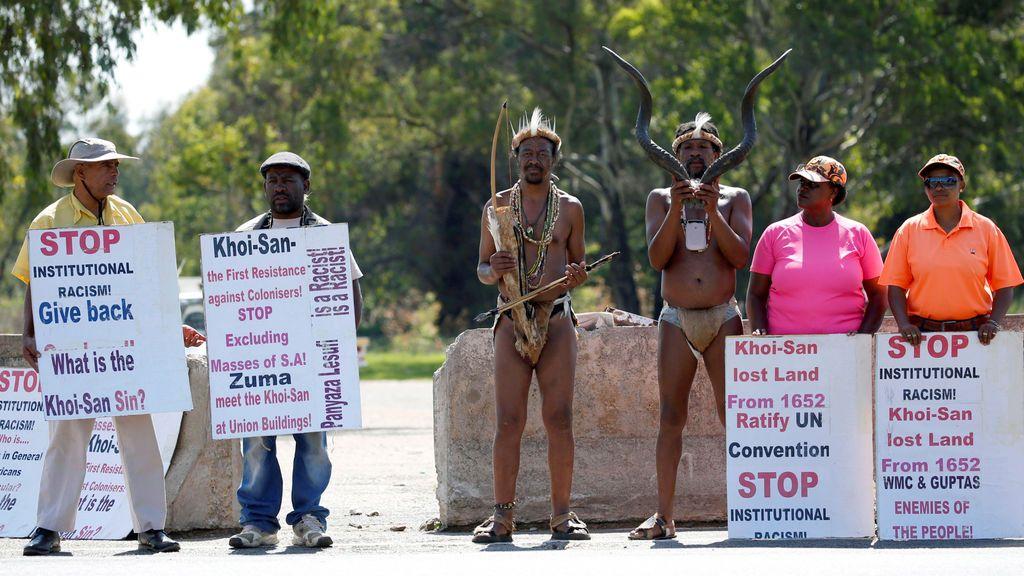 Activistas de KhoiSan se colocan al lado de pancartas fuera del lugar de celebración de la 54ª Conferencia Nacional del Congreso Nacional Africano (ANC) en el Nasrec Expo Center en Johannesburgo, Sudáfrica