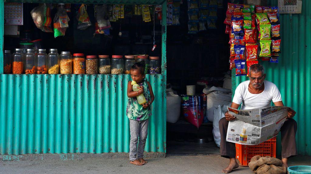 Una niña reacciona cuando un tendero lee un periódico afuera de su tienda en un barrio marginal en Mumbai