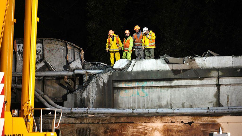 Los trabajadores examinan una sección de puente dañada en el lugar del descarrilamiento del tren 501 de Amtrak en Dupont, Washington, EE. UU