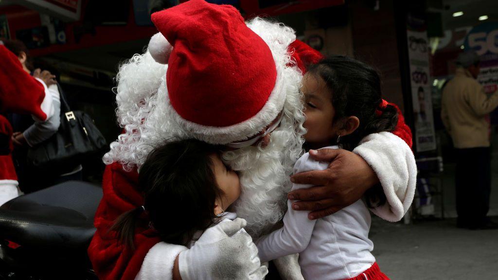 Un miembro de la policía de tránsito vestido de Santa Claus abraza a los niños en el centro de Monterrey, México