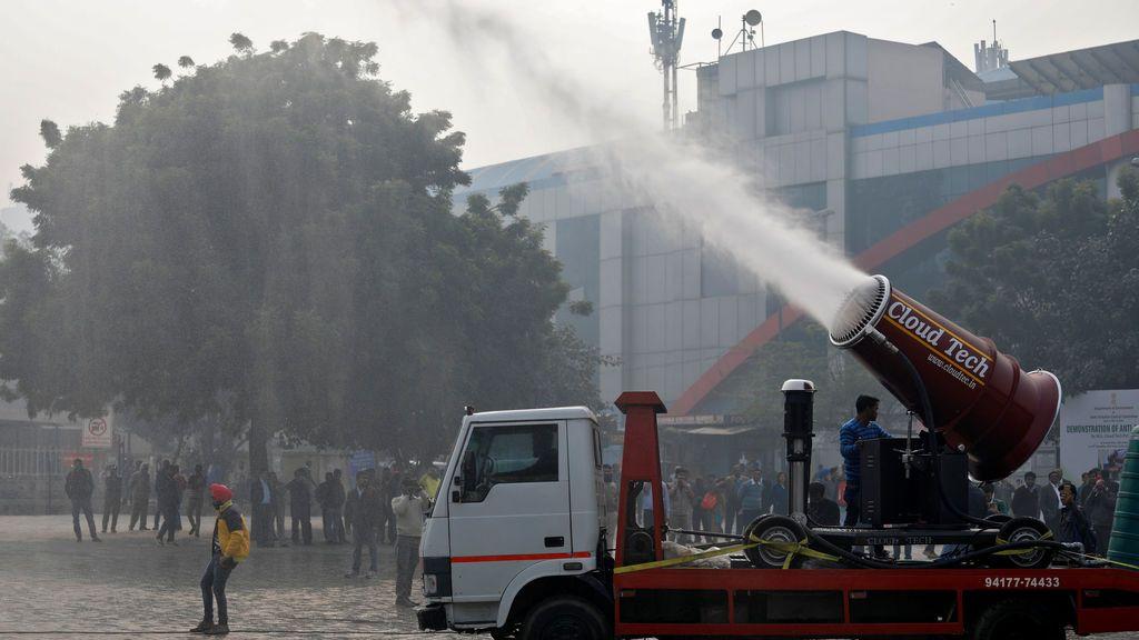 """Un hombre opera una """"pistola anti-smog"""", una máquina que pulveriza agua atomizada en el aire para reducir la contaminación, durante su prueba organizada por el Departamento de Medio Ambiente y el Comité de Control de la Contaminación de Delhi en una terminal de autobuses en Nueva Delhi, India"""