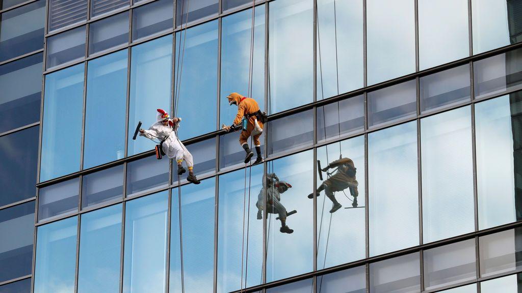 Los limpiadores de ventanas, disfrazados de gallo, el zodíaco chino de este año y un perro, el nuevo animal zodiacal chino del próximo año, posan para los fotógrafos mientras limpian las ventanas del hotel Ryumeikan durante un evento promocional para celebrar el próximo año nuevo en Tokio, Japón