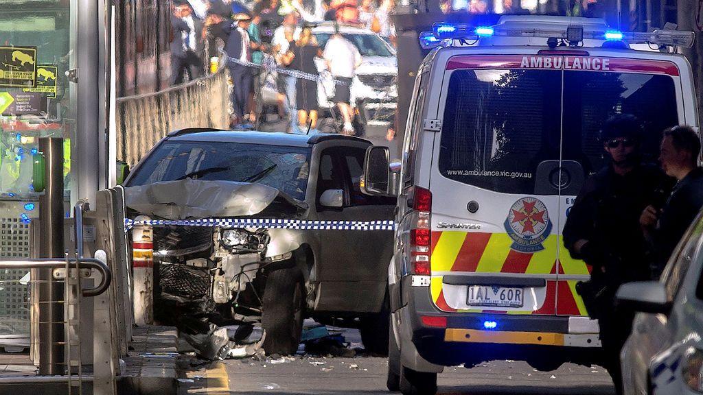 La policía australiana permanece cerca de un vehículo accidentado después de que arrestaron al conductor de un vehículo que se estrelló contra los peatones en una intersección atestada cerca de la estación de tren Flinders Street en el centro de Melbourne, Australia