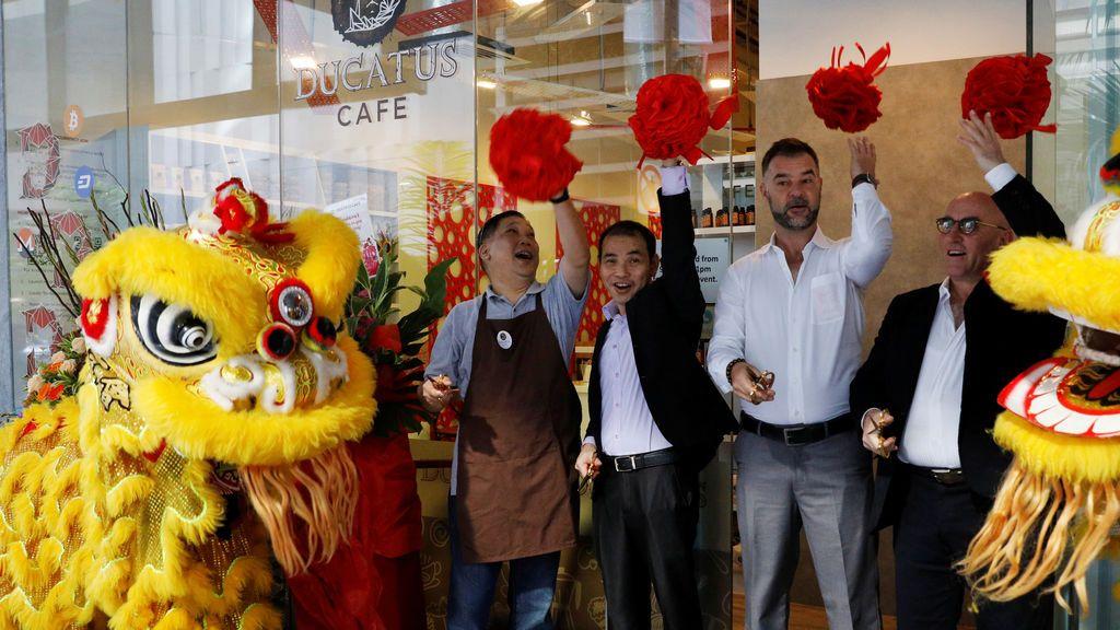 El CEO de Ducatus Ronny Tome (2nd R) abre su cafetería sin dinero en efectivo que acepta criptomonedas como Bitcoin en Singapur
