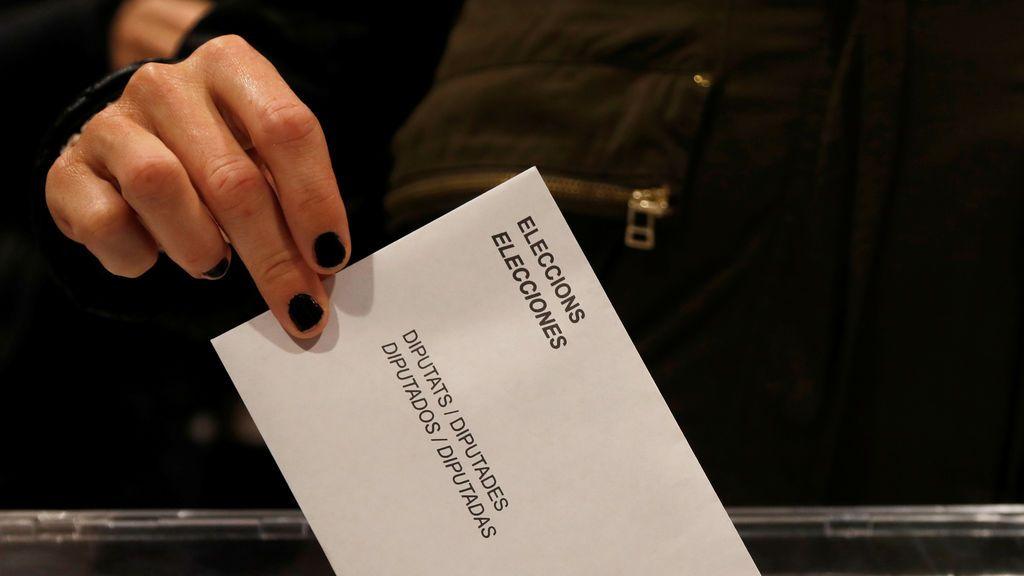 Una mujer presenta su voto en las elecciones regionales de Cataluña en un colegio electoral