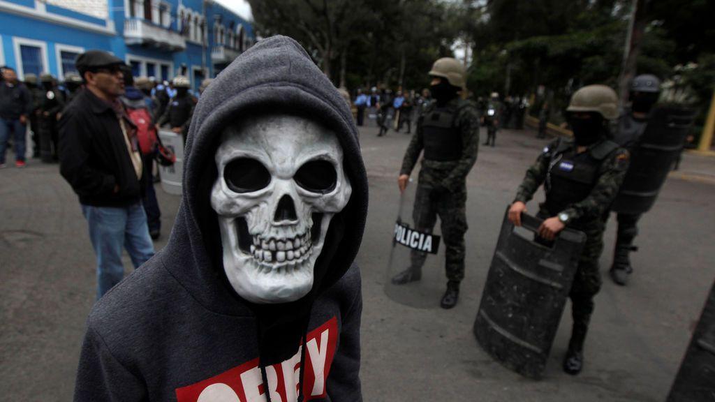 Un partidario de la oposición que llevaba una máscara de calavera estaba parado frente a la policía militar durante una protesta por unas elecciones presidenciales impugnadas con acusaciones de fraude electoral en Tegucigalpa, Honduras