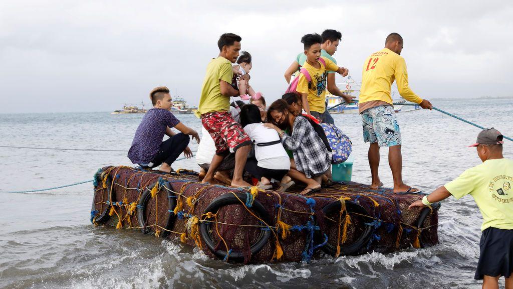 Los pasajeros varados viajan en una balsa improvisada después de que se cancelaron todos los servicios del ferry, un día después de que un buque filipino zozobró debido al mal tiempo en Infanta, Quezon en Filipinas