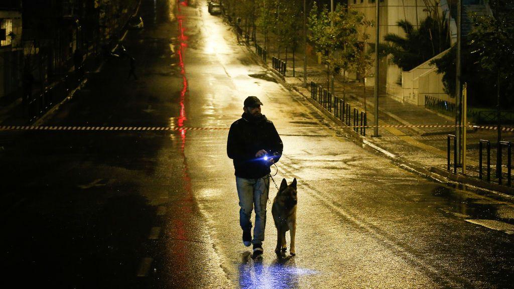 Un oficial de policía con un perro rastreador busca evidencia a lo largo de una carretera después de la explosión de una bomba en un edificio de la corte en Atenas, Grecia
