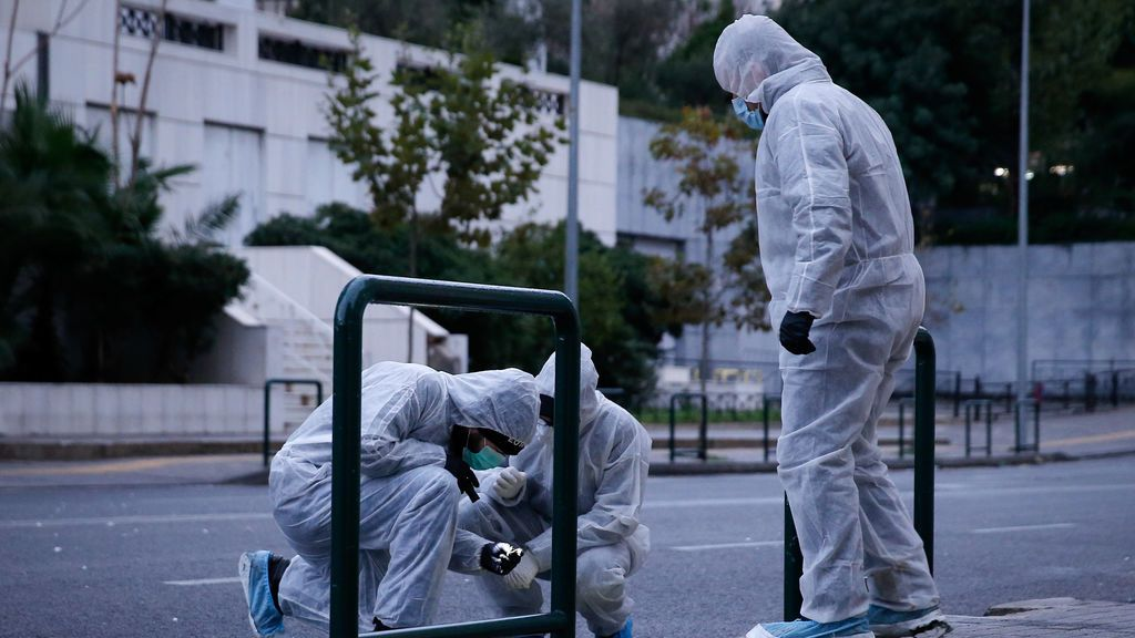 Los agentes de policía buscan evidencia después de la explosión de una bomba en un edificio del Tribunal en Atenas, Grecia