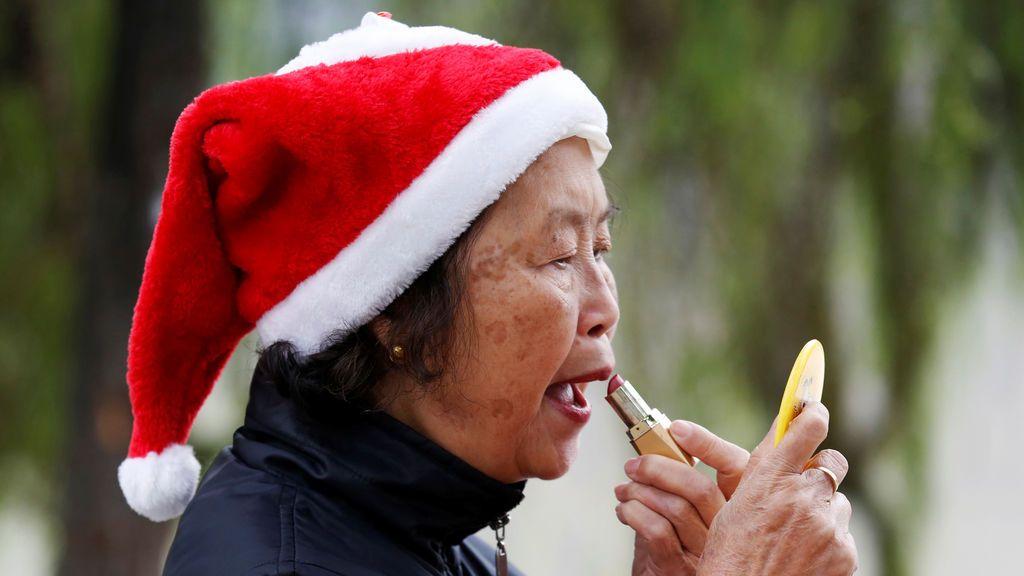 Una mujer vestida con un traje de Santa Claus se maquilla en el lago Hoan Kiem en Hanoi, Vietnam