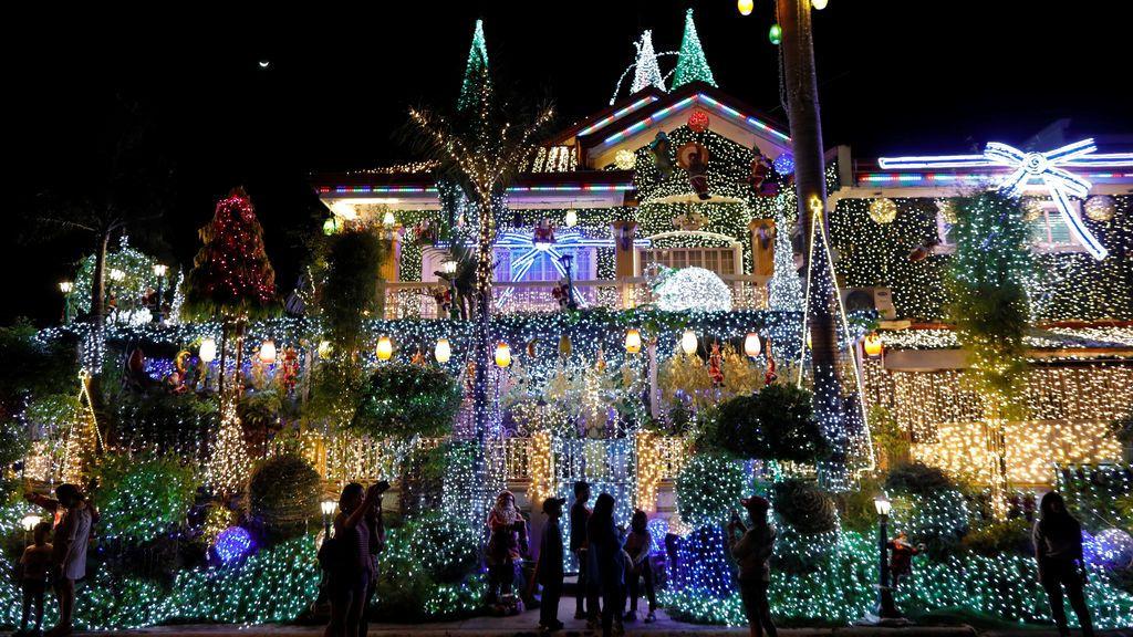 La gente se hace fotos con una casa llena de luces con motivos navideños en Rizal, Manila