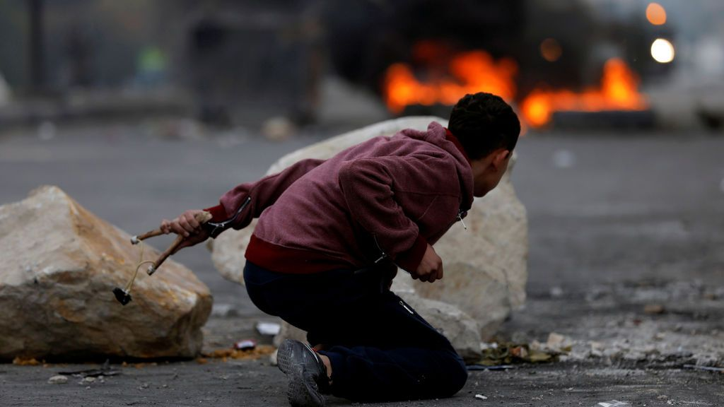 Un palestino se cubre durante los enfrentamientos con las tropas israelías