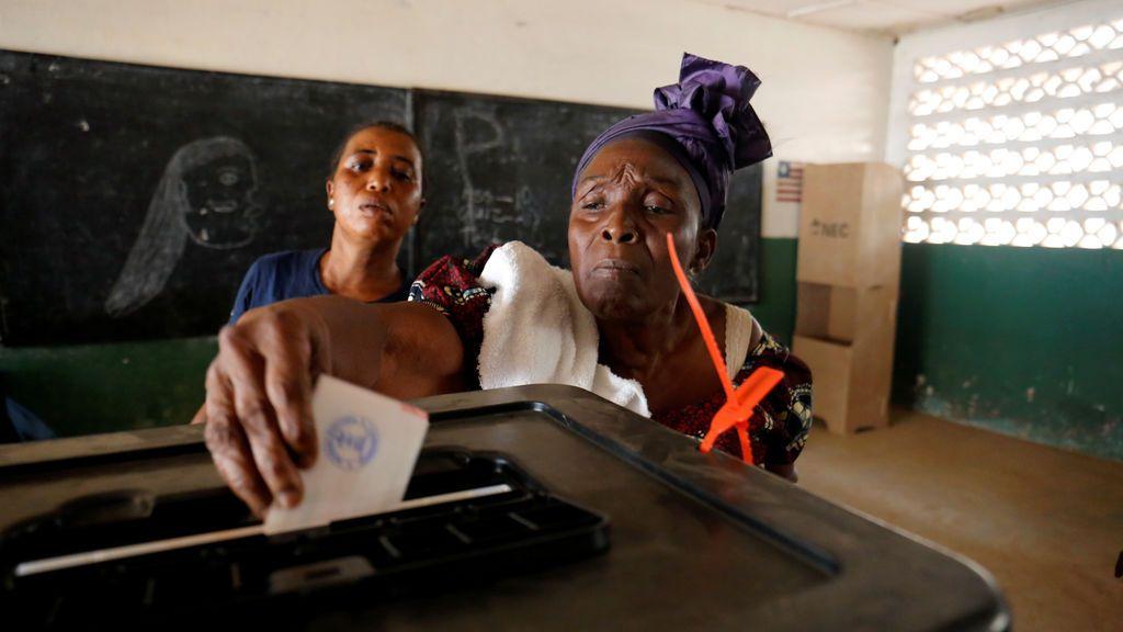 Una mujer presenta su voto durante las elecciones presidenciales en un colegio electoral en Monrovia, Liberia