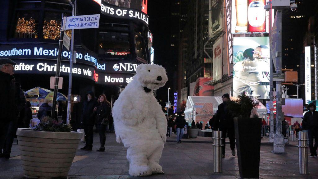 Una persona vestida con un traje de oso polar se sienta solo en Navidad en Times Square en Nueva York