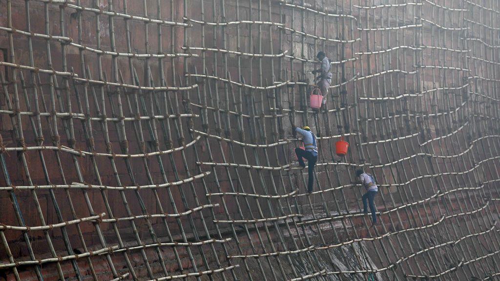 Los trabajadores suben andamios para limpiar las paredes del histórico Fuerte Rojo en los barrios antiguos de Delhi, India