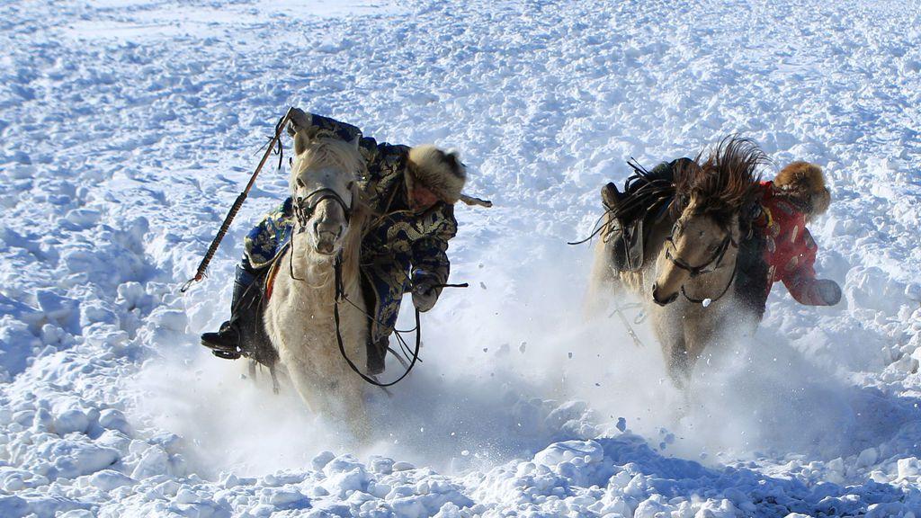 Los pastores domestican caballos en un pasto cubierto de nieve en Xilingol, Región Autónoma de Mongolia Interior, China