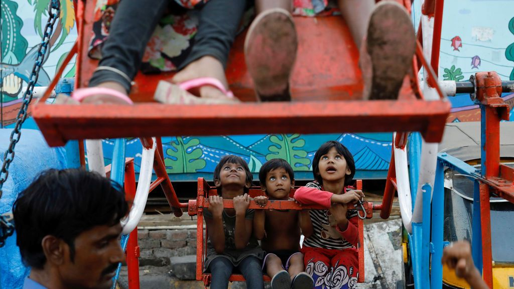 Niños montan en ferris operados manualmente en un barrio de Mumba, India