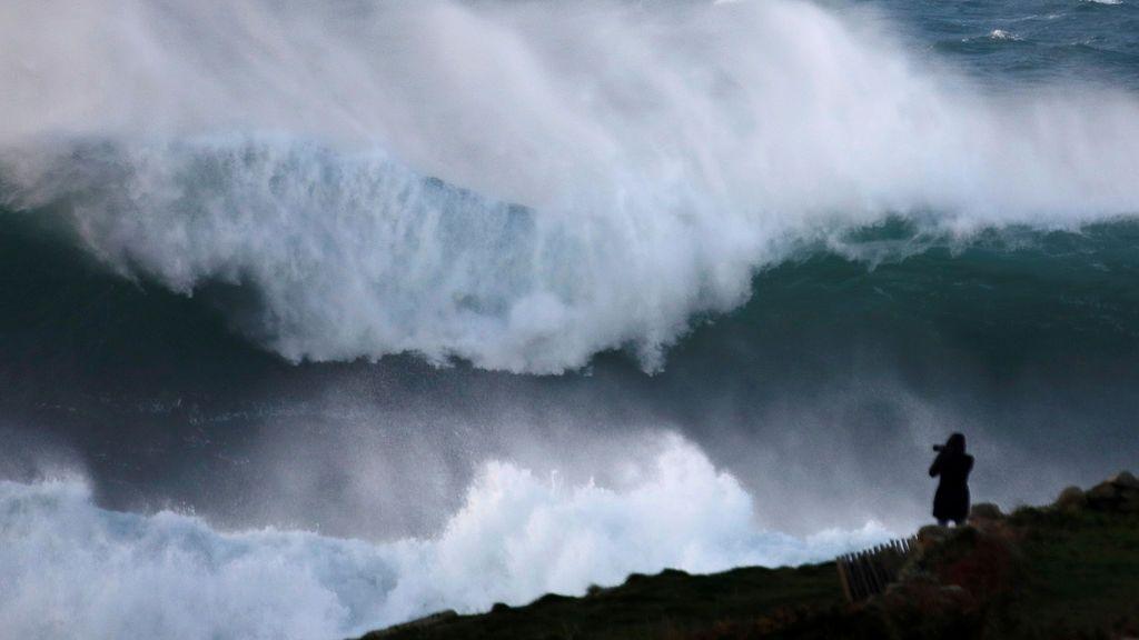 Una mujer fotografía las olas rompiendo en Audierne, al oeste de Francia