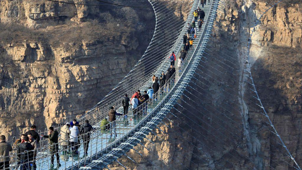 Los visitantes caminan por el puente colgante de cristal recién abierto de 488 metros de largo en la atracción Hongyagu en Pingshan, provincia de Hebei, China