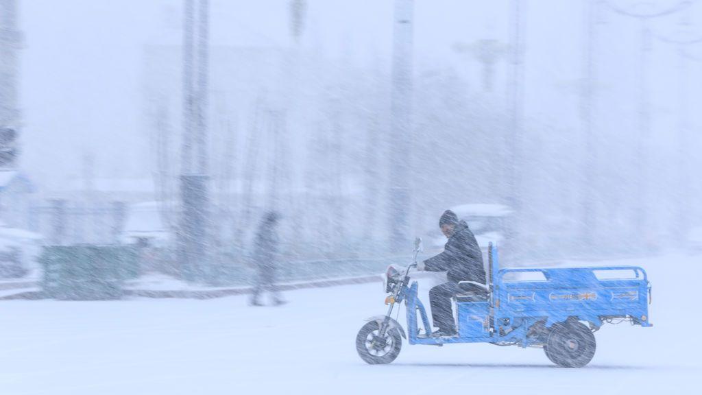 Un hombre monta un vehículo en medio de fuertes nevadas en Beitun, Región Autónoma Uygur de Xinjiang, China