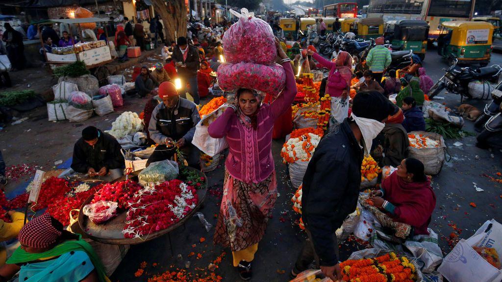 Una mujer lleva guirnaldas de flores durante la madrugada en un mercado de flores al por mayor en Ahmedabad, India