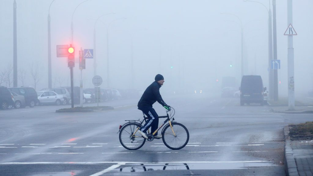 Un hombre monta una bicicleta durante la niebla pesada en Minsk, Bielorrusia