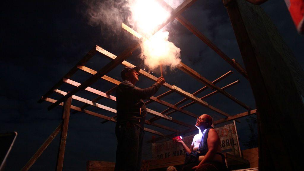 Haydee Mestre (R) y su esposo Carlos Rosario encienden fuegos artificiales durante la víspera de Año Nuevo en lo que solía ser su dormitorio antes de que el huracán María azotara la isla en septiembre, en Morovis, Puerto Rico