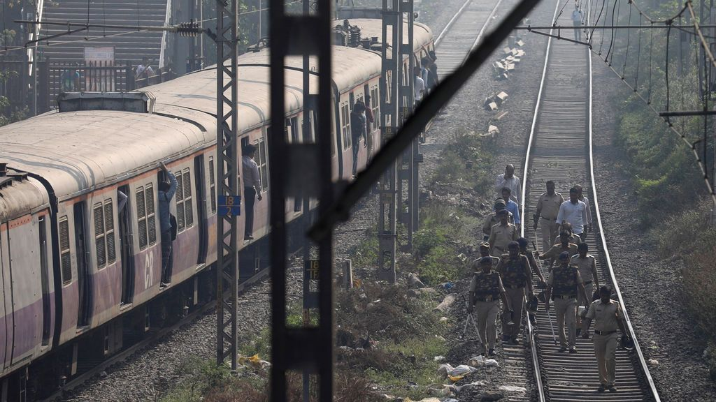 Policías patrullan en pistas en una estación de tren suburbano en Mumbai, India