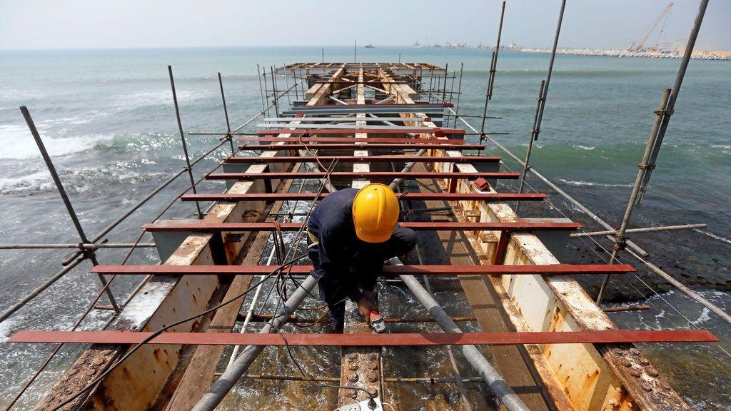 Un obrero trabaja en un sitio de construcción de un puente sobre el mar en Colombo, Sri Lanka